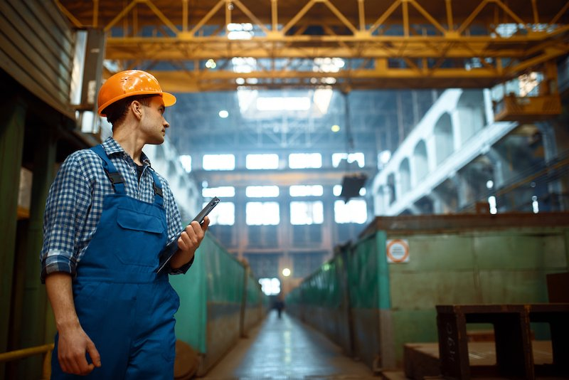 Master looks at the work of the crane operator on metal factory. Metalworking industry, industrial manufacturing of steel production